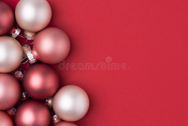 Decoração esbranquiçado cor-de-rosa do feriado das bolas do Natal da pérola de Borgonha no fundo carmesim vermelho contínuo Criat fotos de stock royalty free