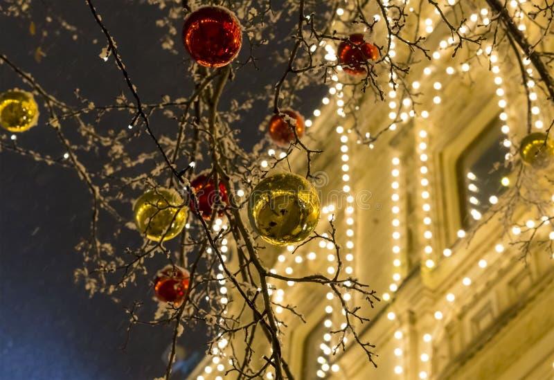 Decoração festiva da rua da cidade para bolas brilhantes brilhantes do Natal e do ano novo do vermelho dourado em árvores fotografia de stock royalty free