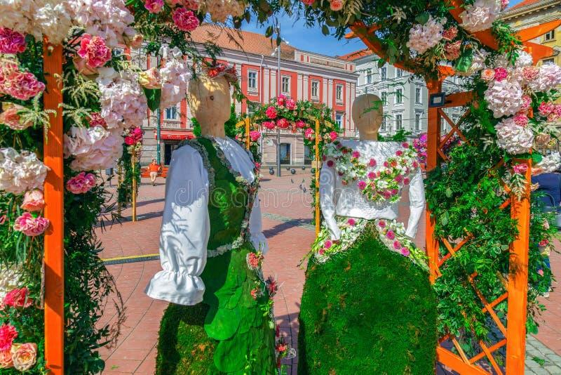 A decoração floral com as duas estátuas de madeira vestiu-se em um traje popular feito das flores imagem de stock