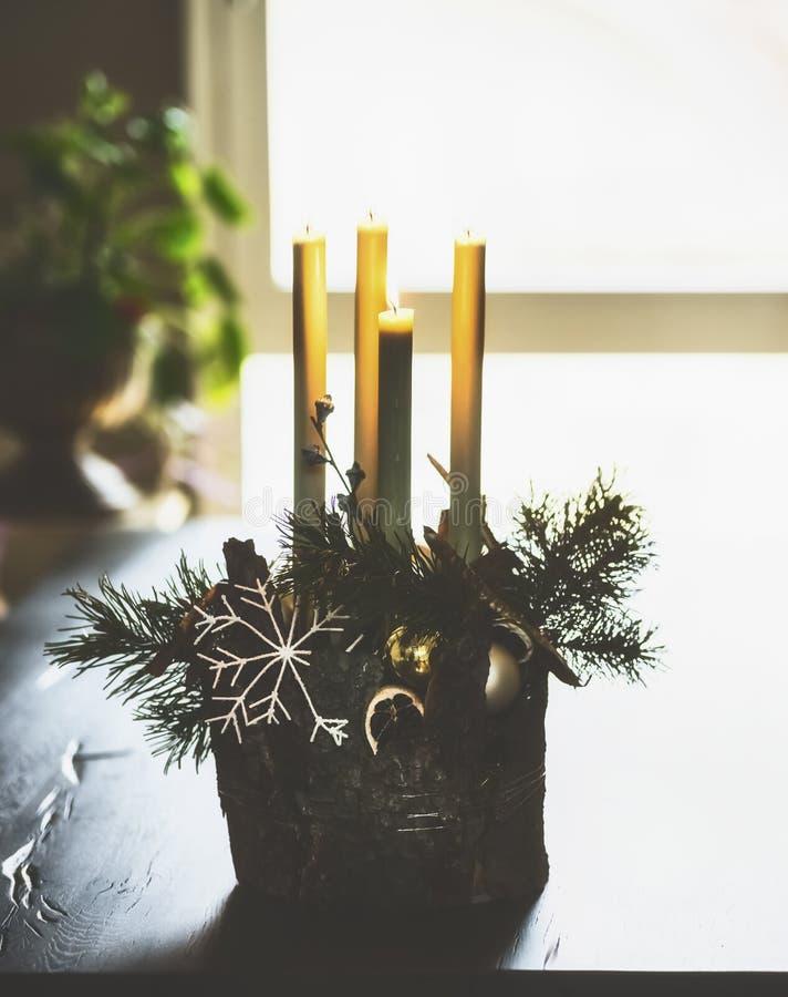 Decoração home do inverno e atmosfera festiva com velas, ramos do abeto e os flocos de neve ardentes na tabela na sala de visitas imagens de stock royalty free