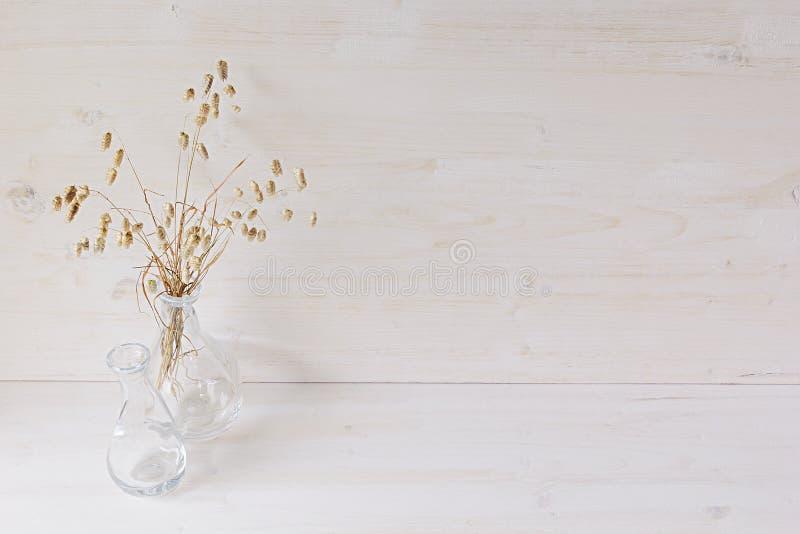 Decoração home macia do vaso de vidro com os spikelets no fundo de madeira branco fotografia de stock royalty free