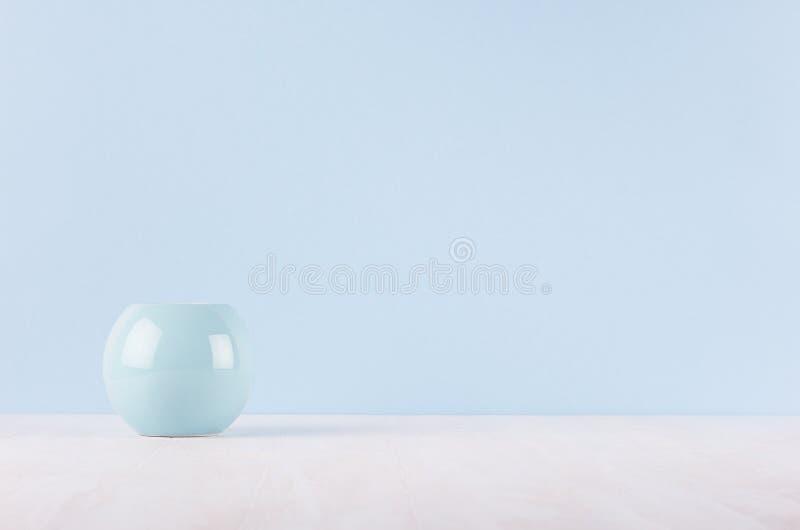 Decoração home moderna elegante do vaso cerâmico liso do círculo na tabela e na luz de madeira brancas - parede azul fotografia de stock