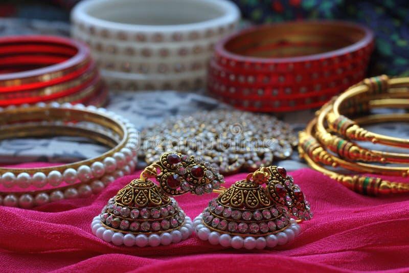 A decoração indiana do cabelo, assim como muitos braceletes e bolas encontram-se em um lenço tradicional colorido imagens de stock