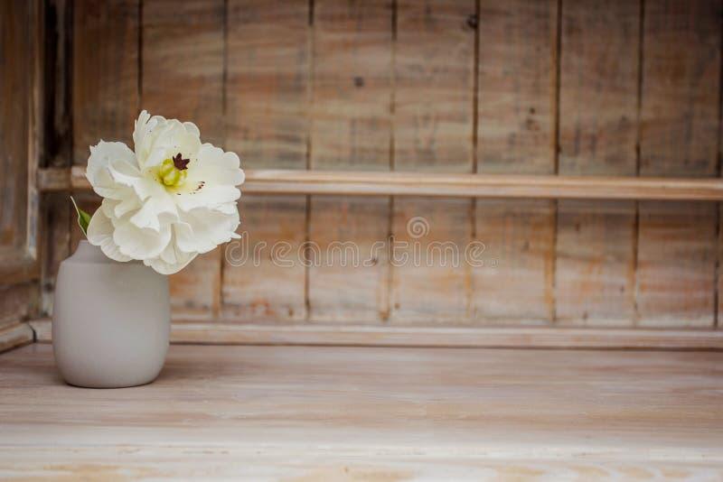 Decoração macia da casa, vaso com a flor pequena branca em um fundo de madeira da parede do vintage branco e em uma prateleira de imagens de stock