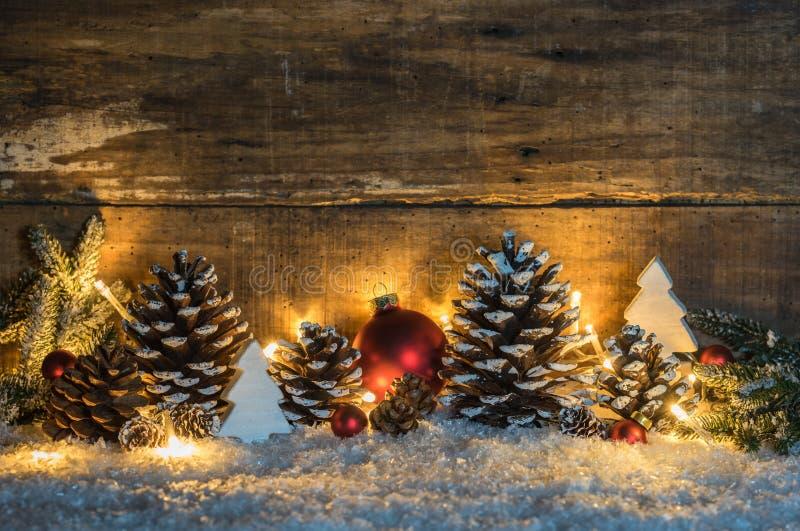 Decoração nevado do Natal com os cones naturais, o verde, as bolas e as luzes do pinho na neve com imagens de stock royalty free