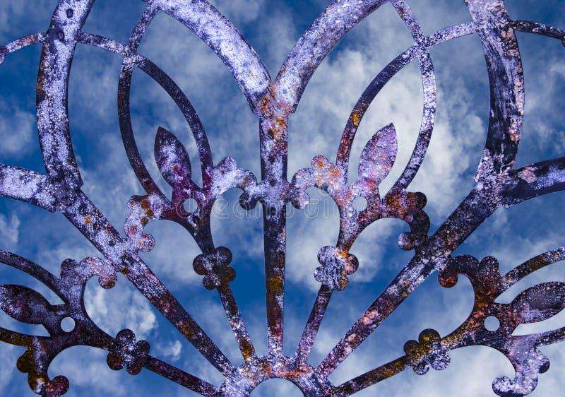 Decoração ou cerca roxa lacey do metal do grunge oxidado do ferro com o céu nebuloso azul que mostra através do fundo imagem de stock