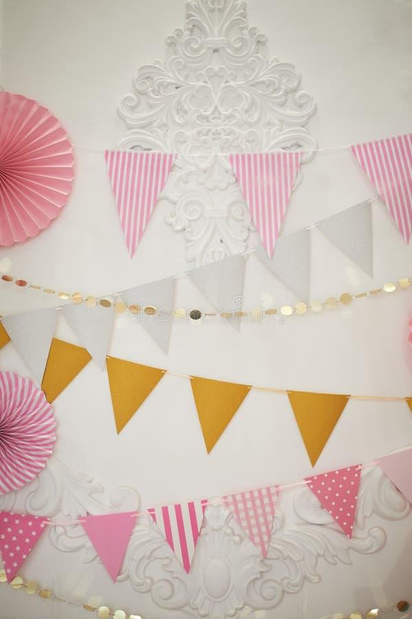 Decoração para o aniversário das crianças, meninas no rosa Bandeiras de papel imagem de stock royalty free