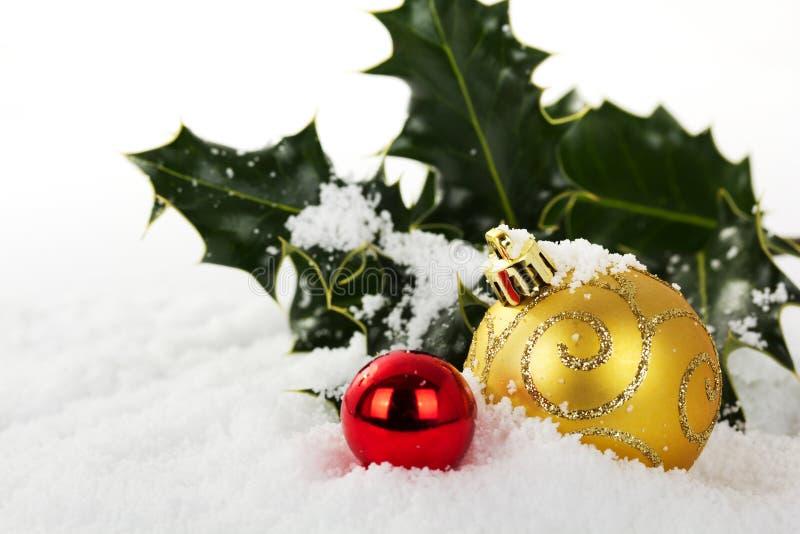 Decorações de Chrismas com azevinho na neve branca foto de stock royalty free