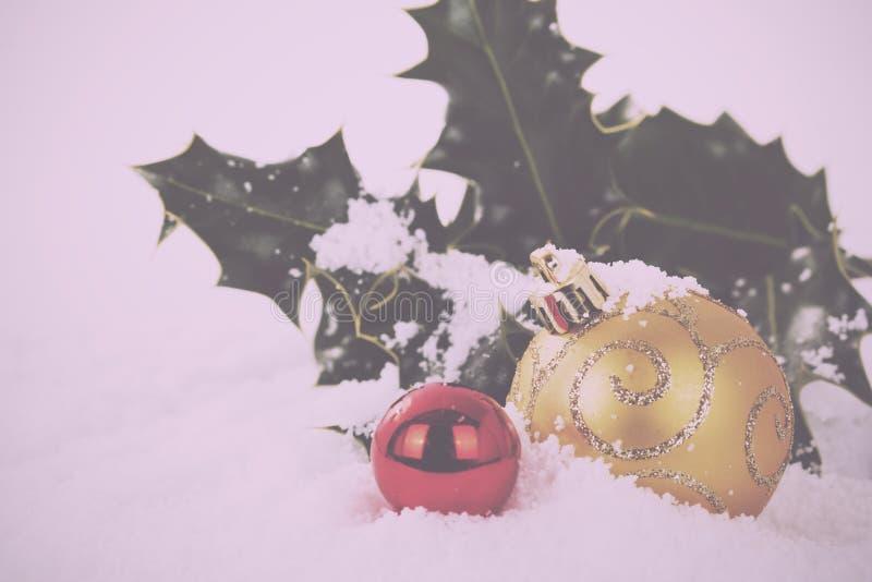 Decorações de Chrismas com azevinho no vintage branco Filt retro da neve fotografia de stock