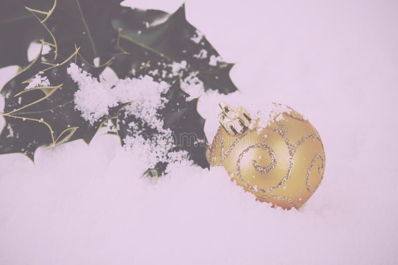 Decorações de Chrismas com azevinho no vintage branco Filt retro da neve fotos de stock royalty free