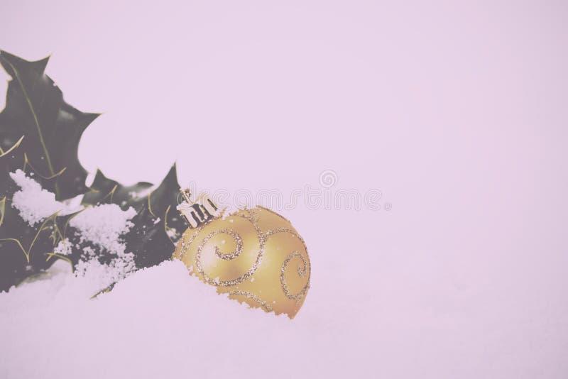 Decorações de Chrismas com azevinho no vintage branco Filt retro da neve foto de stock royalty free