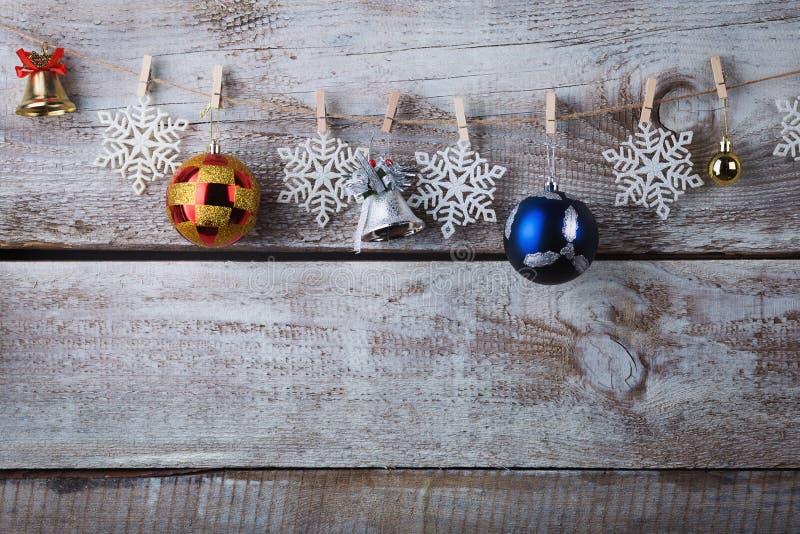 Decorações de Chrismas que penduram na corda no fundo de madeira fotografia de stock royalty free