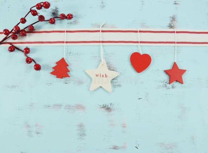 Decorações de suspensão modernas do vermelho e as brancas do Natal no fundo de madeira azul do aqua imagens de stock