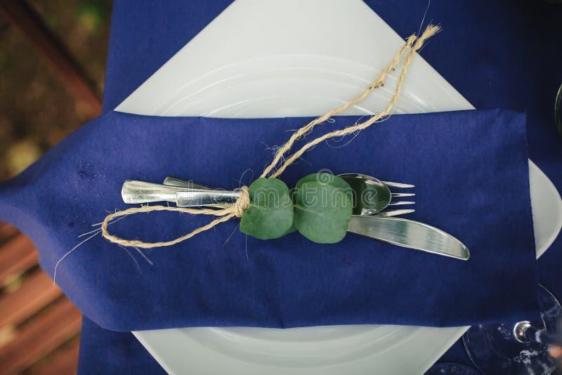 Decorações do casamento em tons azuis Na tabela de madeira nas madeiras há umas hortaliças, cutelaria, eucalipto imagem de stock