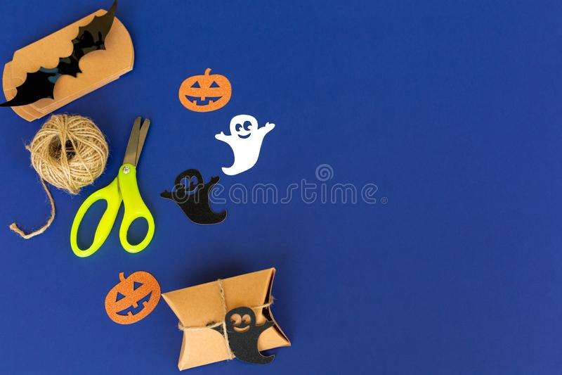 Decorações do Dia das Bruxas, Embalagens de Artesanato, corda, tesoura, abóbora de papel, fantasma sobre fundo azul Presente manu imagem de stock