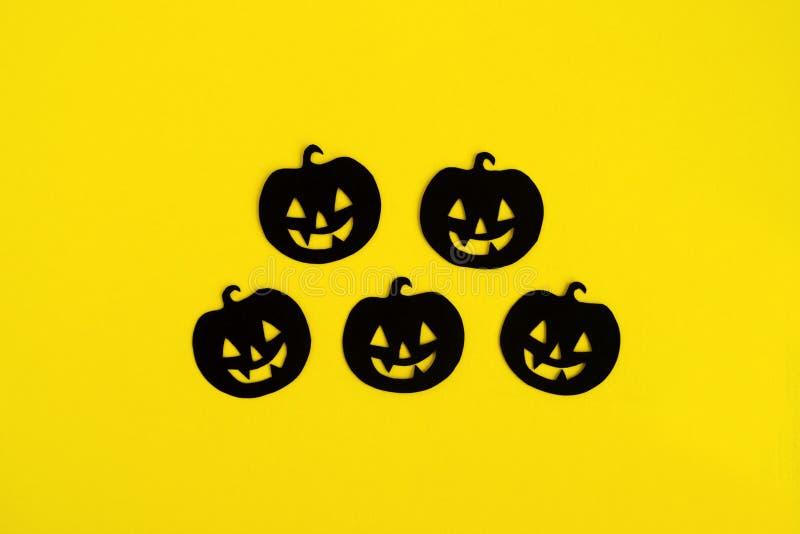 Decorações do feriado para Dia das Bruxas Cinco abóboras de papel pretas em um fundo amarelo, vista superior fotografia de stock royalty free
