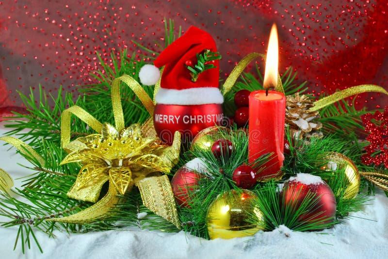 Decorações do Natal com vela e quinquilharias sobre o fundo vermelho imagens de stock royalty free