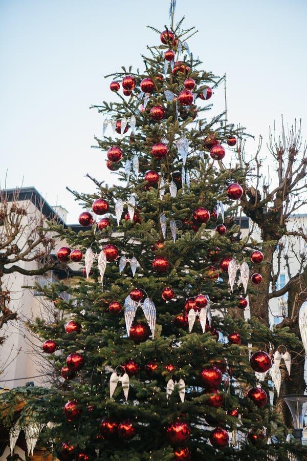 Decorações do Natal em uma árvore de Natal sob a forma das bolas vermelhas e asas do anjo em uma rua na cidade austríaca de imagens de stock royalty free