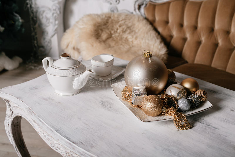 Decorações do Natal na tabela na perspectiva de uma chaminé decorada com ramos spruce e festão foto de stock