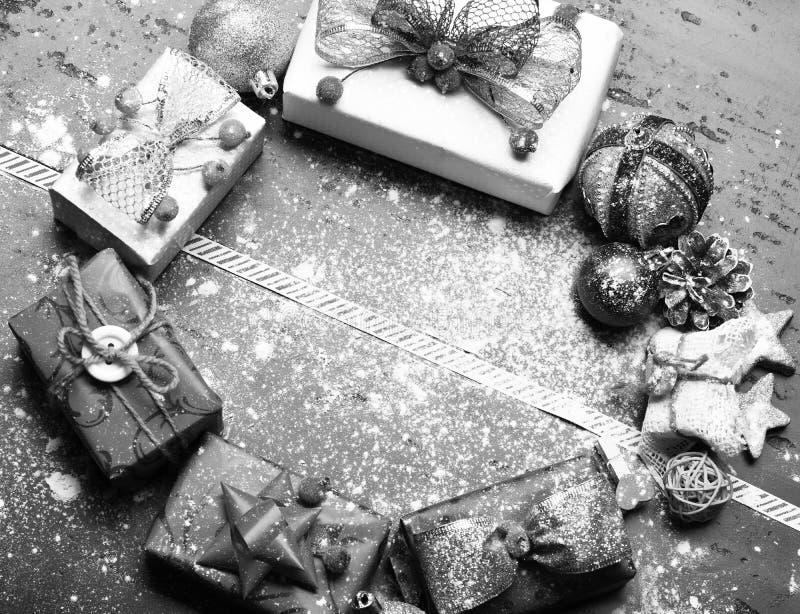 Decorações do Natal no fundo de madeira escuro com neve dispersada A decoração feita de presentes vermelhos, cor-de-rosa e branco fotos de stock royalty free