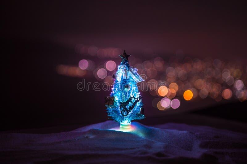 Decorações do Natal Posição da árvore de abeto na neve com feriado bonito fundo decorado e atributos tradicionais do feriado fotografia de stock