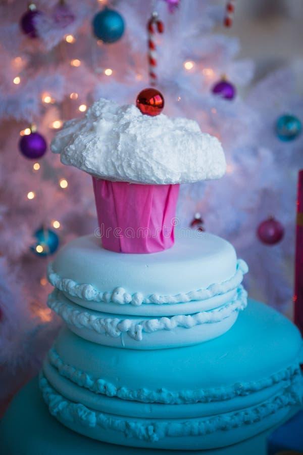 Decorações do Natal sob a forma dos bolos e do grande chocolate Brinquedos do Natal em uma árvore de Natal artificial branca fotografia de stock