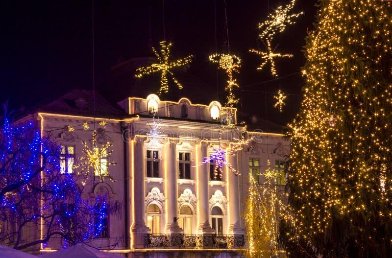 Decorações e luzes do Natal na construção e em torno da construção na noite Árvore de Natal imagens de stock