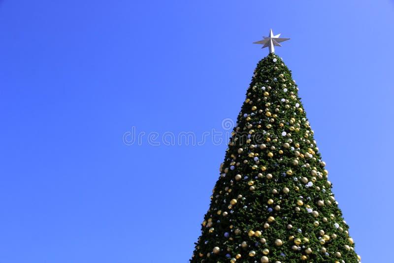 Decorações enormes da árvore de Natal e fundo do céu azul fotos de stock royalty free