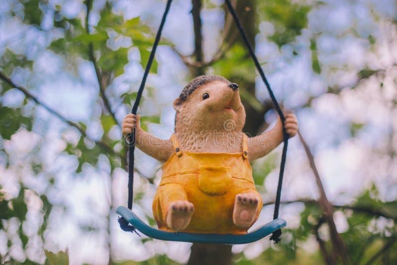 Decora??o da estatueta do jardim do close-up - um ouri?o alegre na roupa amarela que se senta em um balan?o - que pendura em um r fotografia de stock
