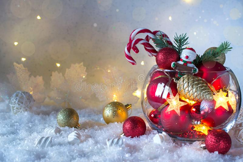 Decoración brillante de la Navidad o del Año Nuevo en el florero de cristal con los bastones de caramelo en fondo de la nieve Tar foto de archivo libre de regalías