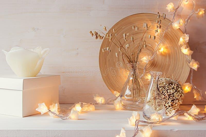 Decoración casera de la Navidad con las luces ardientes en el fondo de madera blanco imagenes de archivo