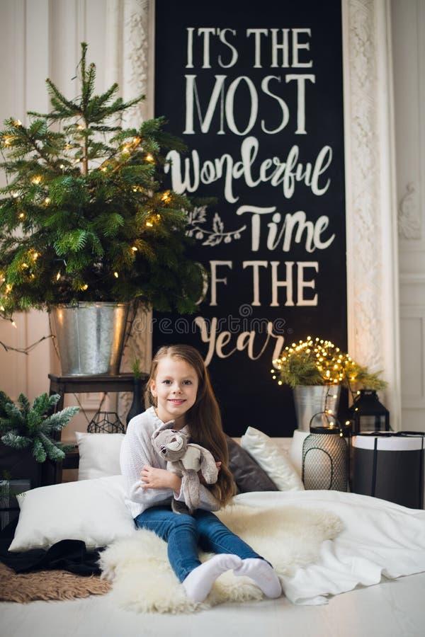 Decoración casera de la Navidad Una muchacha de la niña que se sienta en una tela escocesa en un piso Muchacha muy hermosa que ju foto de archivo libre de regalías