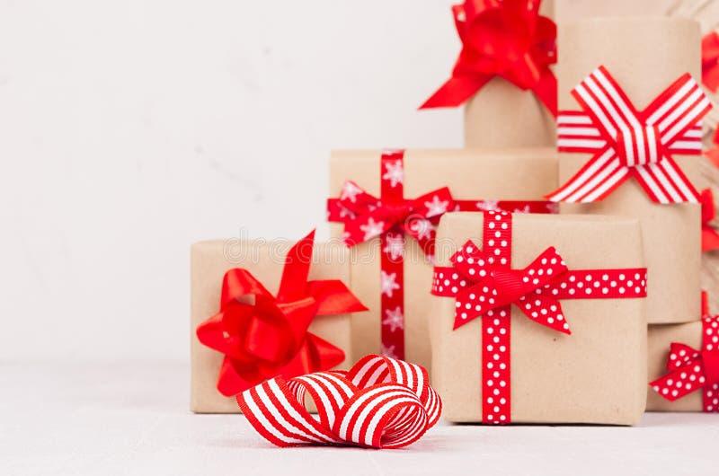 Decoración casera festiva con muchas cajas de regalo de Kraft con las cintas rojas en el tablero de madera blanco, espacio de la  fotos de archivo
