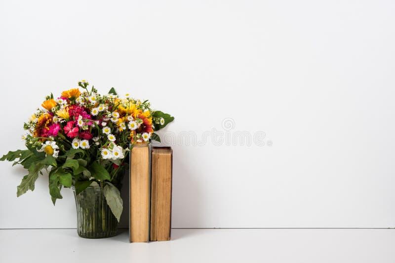 Decoración casera interior con las flores y los libros, decoración simple del verano imagen de archivo