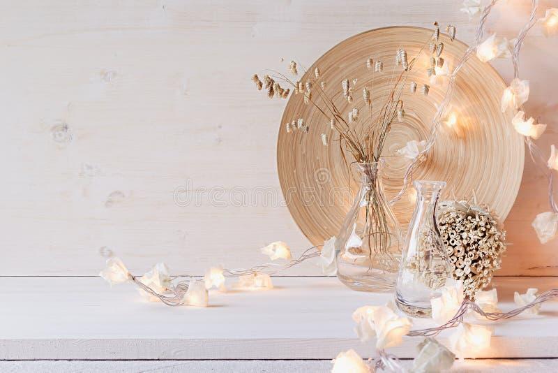 Decoración casera suave con las luces ardientes en el fondo de madera blanco foto de archivo
