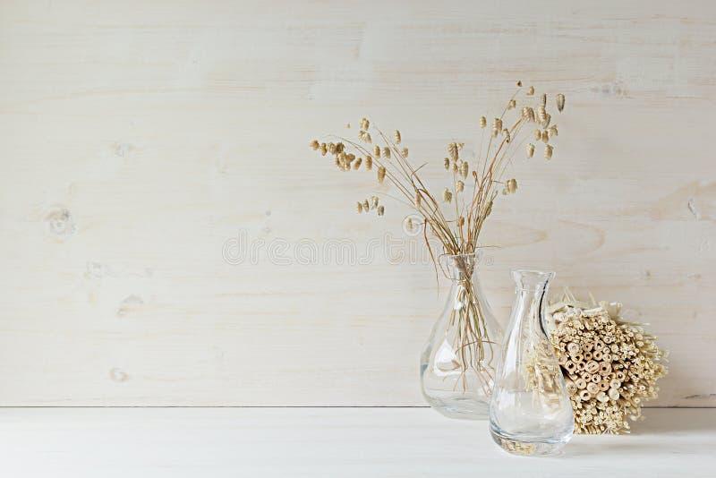 Decoración casera suave del florero de cristal con las espiguillas y los tallos en el fondo de madera blanco fotografía de archivo libre de regalías