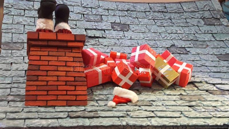 Decoración creativa Santa& x27 de la Navidad; botas de s presentes en la chimenea del tejado imagen de archivo