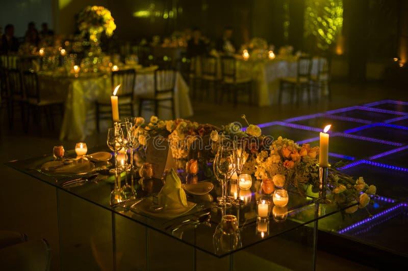 Decoración de la boda de la noche con las velas y las flores naturales imagen de archivo