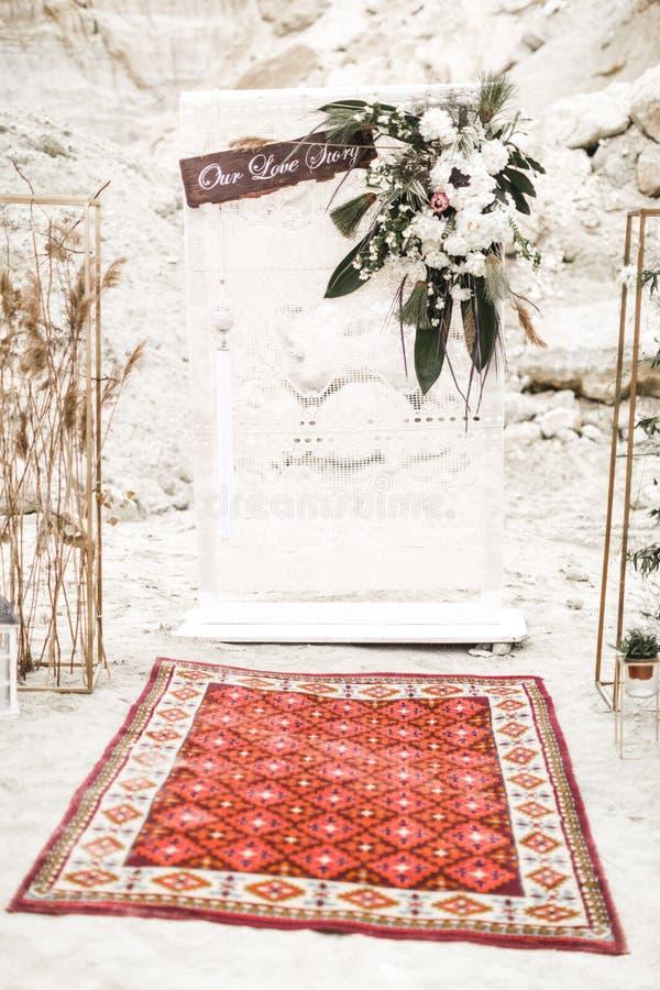 Decoración de la boda en el estilo de un boho Arco de la boda, adornado con el paño y las flores blancos, alfombra roja, visitand imagenes de archivo