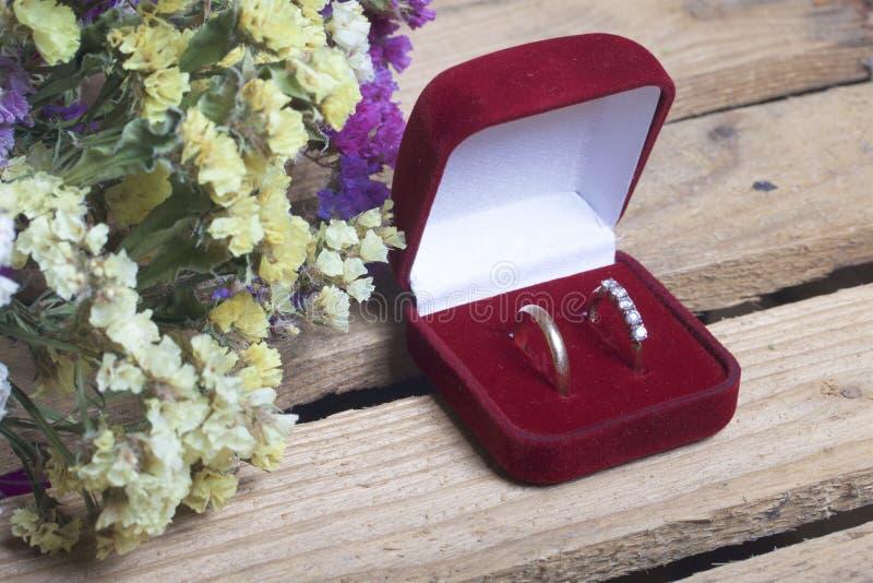 Decoración de la boda Los anillos de bodas en caja mienten en una caja de madera Un ramo de flores secadas cerca foto de archivo libre de regalías