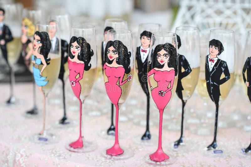 Decoración de la boda, vidrios de vino y flautas de champán en el vector Flautas de champán pintadas como mujeres y hombres Vidri imagen de archivo