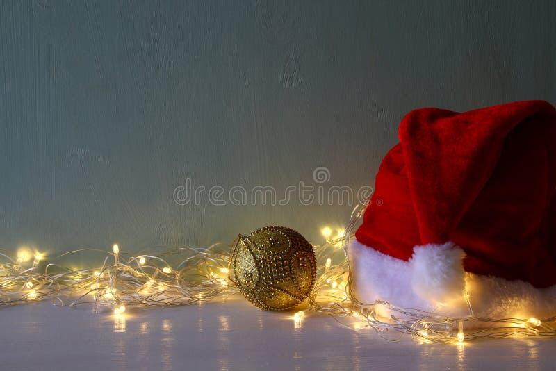 decoración de la bola del oro de la Navidad con las luces calientes de la guirnalda fotografía de archivo