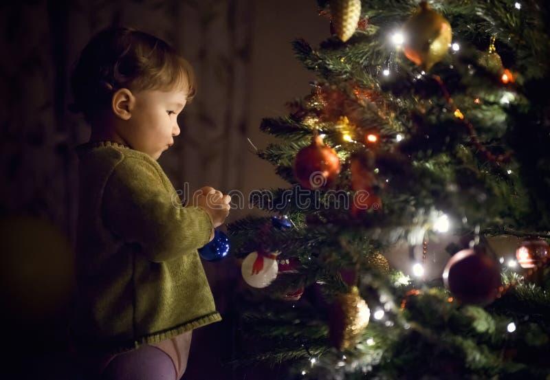 Decoración de la ejecución del lis del niño en el árbol de navidad fotos de archivo libres de regalías