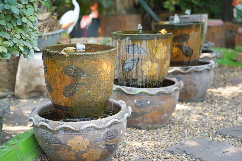 Decoración de la fuente del tarro en el jardín fotos de archivo