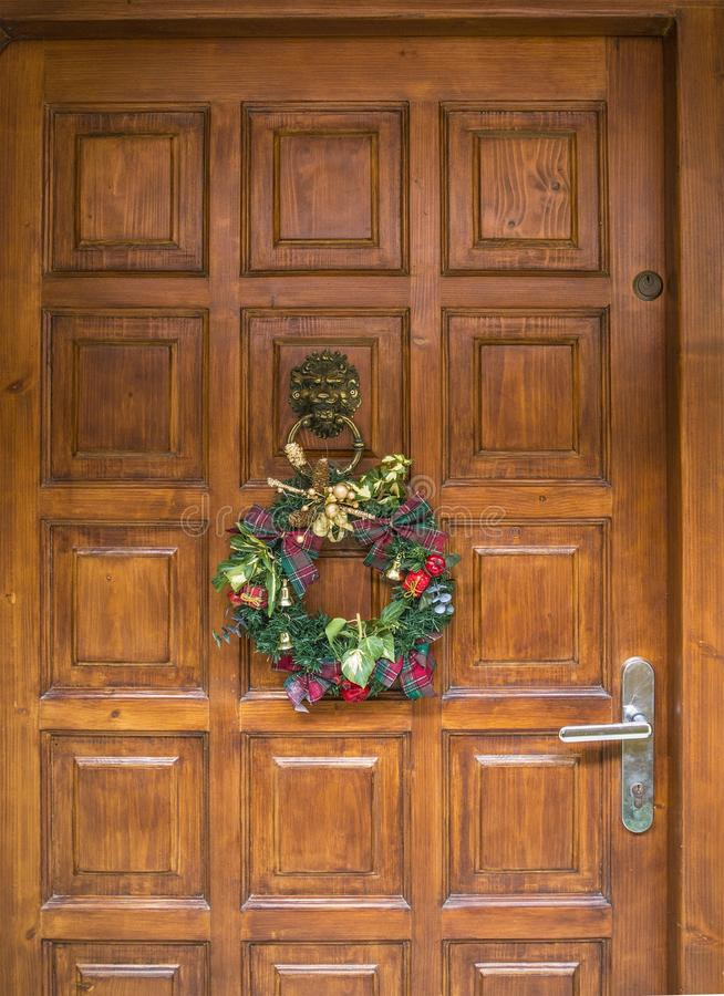 Decoración de la guirnalda de la Navidad en la puerta de entrada de madera fotografía de archivo