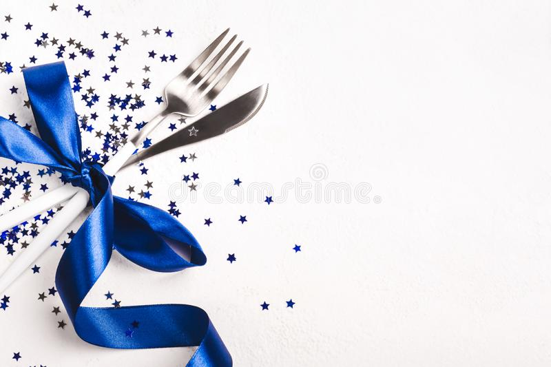 Decoración de la mesa de Navidad decorada con una cinta azul fantasma y las estrellas confetti sobre fondo blanco fotografía de archivo libre de regalías