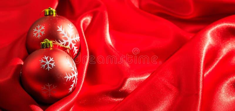 Decoración de la Navidad Bolas de la Navidad en el fondo rojo del satén, bandera fotografía de archivo