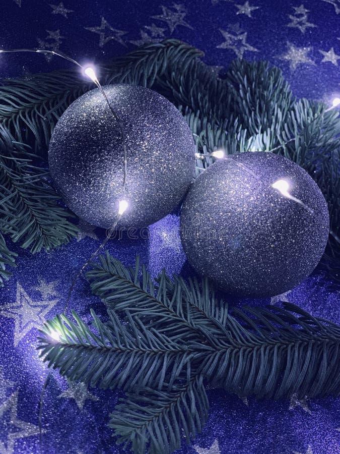 Decoración de la Navidad: bolas de plata con los conos y las ramas de árbol de abeto aisladas en fondo de las estrellas imagen de archivo libre de regalías