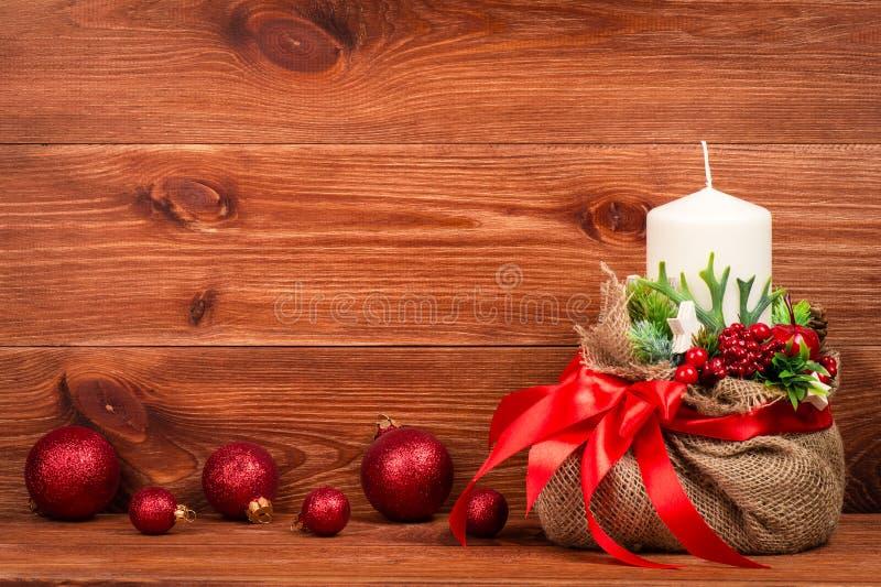 Decoración de la Navidad - composición de la Navidad con el bolso, la vela blanca y las bolas en el fondo de madera fotografía de archivo