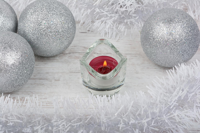 Decoración de la Navidad con la vela roja en el fondo de madera blanco imagen de archivo